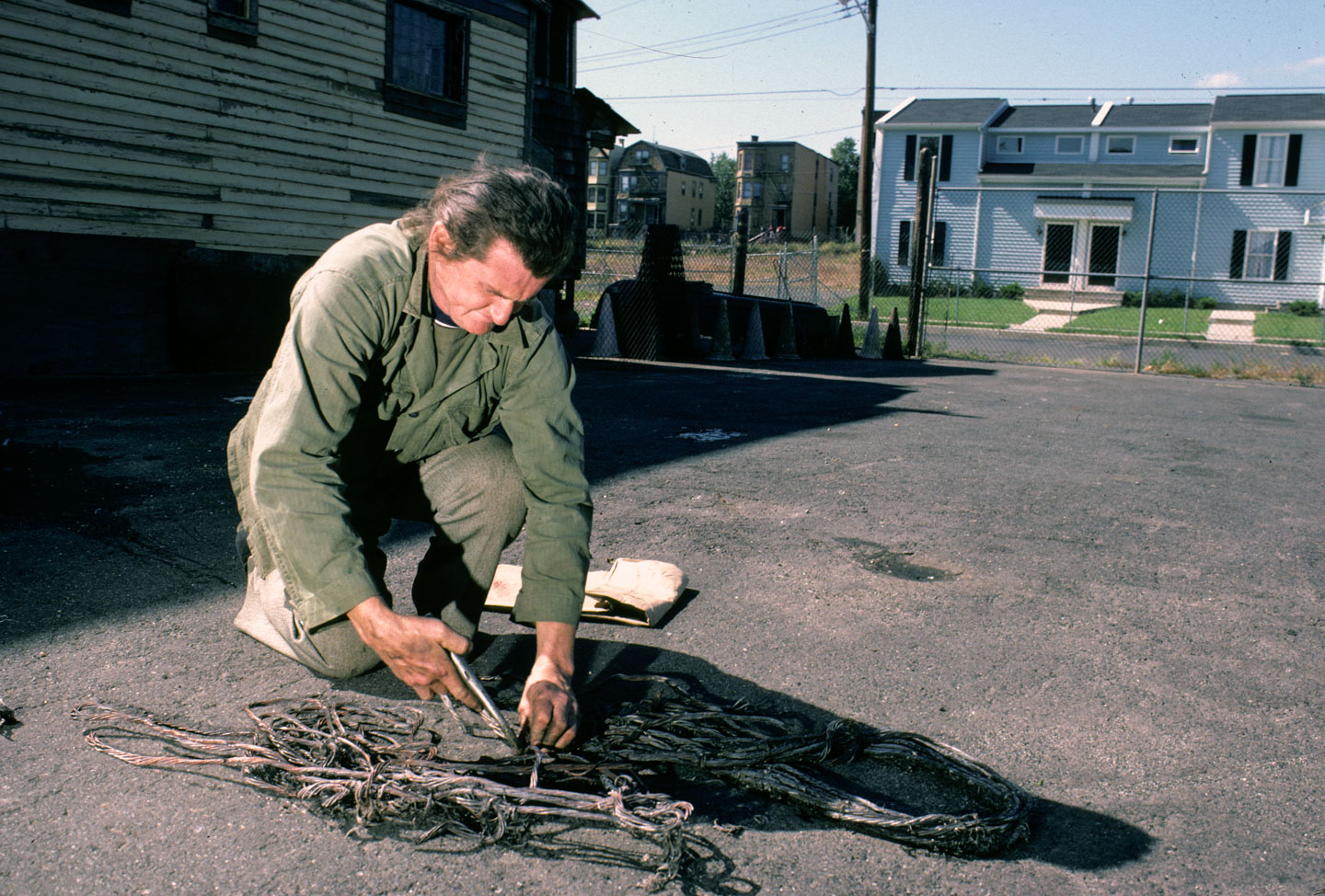 14-Kea Tawana separating copper from brass in peeled cables to sell to a junk dealer, Orange at 14th, Newark, 1987_